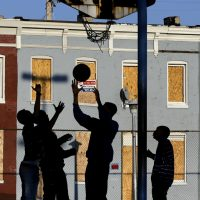 Countless Americans are living on virtually no income. The shocking fact of these families and the complex strategies they use to survive is a national disgrace, says Renée Loth. In this photo, children play basketball at a park near blighted row houses in Baltimore, Monday, April 1, 2013. (Patrick Semansky/ AP)