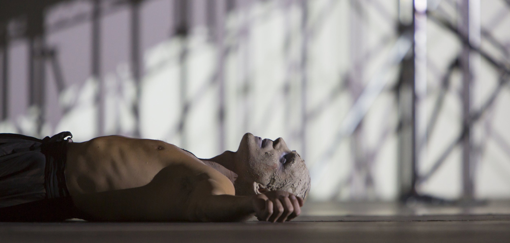 """Yury Yanowsky lay prone and exhausted in Boston Lyric Opera's production of Philip Glass' """"In the Penal Colony."""" (T. Charles Erickson/Boston Lyric Opera)"""