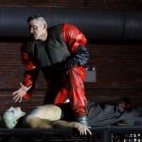 "David McFerrin threatens Yury Yanowsky in Boston Lyric Opera's production of Philip Glass's ""In the Penal Colony."" (T. Charles Erickson/Boston Lyric Opera)"