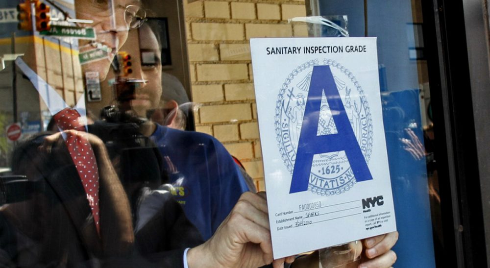 """In this July 28, 2010 file photo, New York City Health Commissioner Thomas Farley post the health department's first """"A"""" grade award for sanitary conditions on the window of Spark's Deli in Long Island City, N.Y. (Bebeto Matthews/ AP)"""