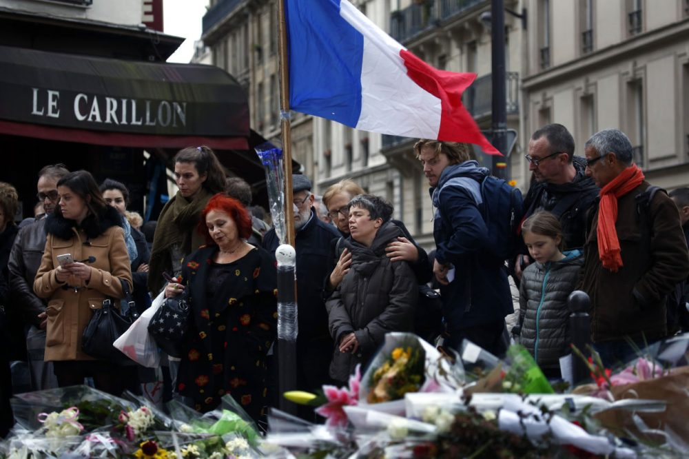 People gather in front of Le Carillon cafe, a site of the recent attacks in Paris. (Jerome Delay/AP)