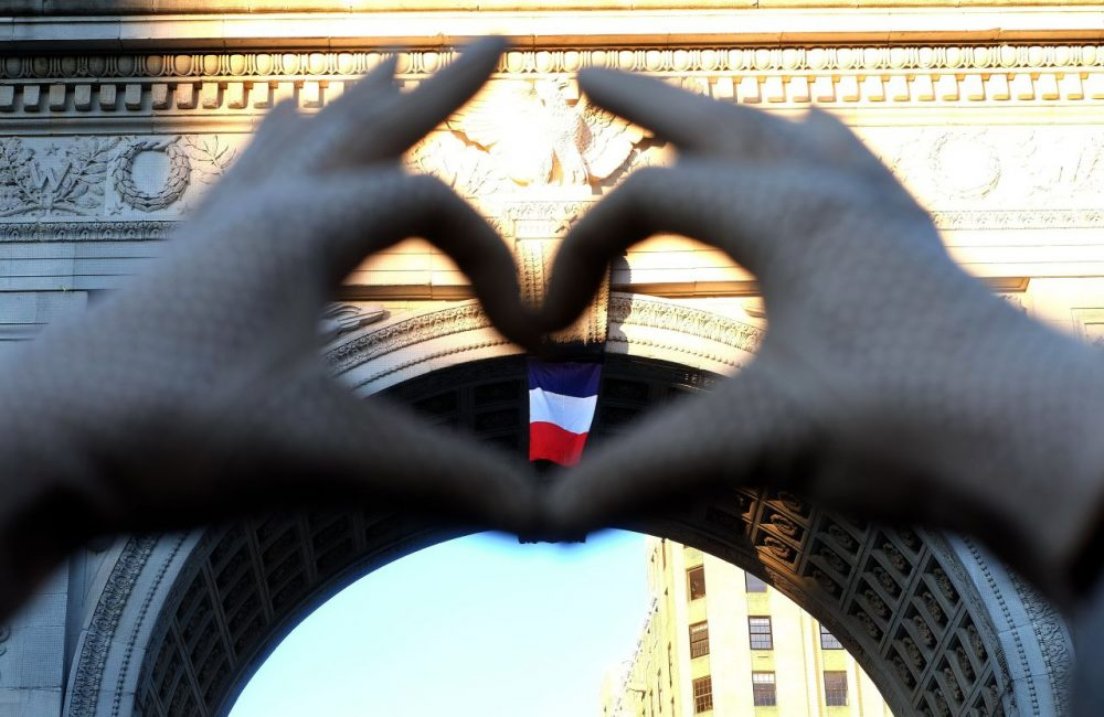 A woman makes a heart sign with her fingers framing a French national flag placed on the arch at the Washington Square Park during a vigil to show solidarity with the citizens of France on November 14, 2015 in New York, a day after the Paris terrorist attacks. Islamic State jihadists claimed a series of coordinated attacks by gunmen and suicide bombers in Paris on November 13 that killed at least 129 people in scenes of carnage at a concert hall, restaurants and the national stadium. (Jewel Samad/AFP/Getty Images)