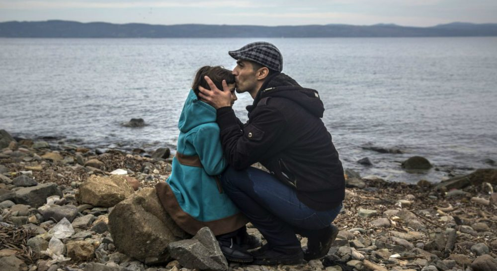 """Eileen McNamara: """"If they are not the embodiment of the promise engraved on the Statue of Liberty, who exactly are the 'huddled masses yearning to breathe free' that Emma Lazarus described?"""" In this photo, a Syrian man kisses his daughter shortly after disembarking from a dinghy at a beach on the Greek island of Lesbos, Monday, Nov. 16, 2015. (Santi Palacios/AP)"""