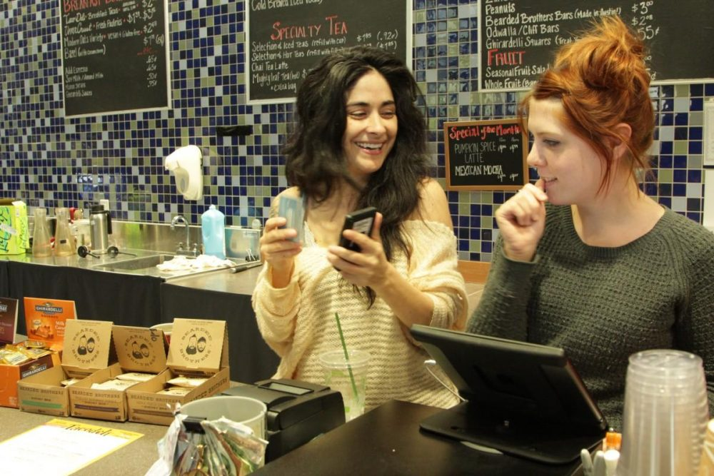 Baristas Sarah Castro (left) and Caitlyn Feeney take coffee orders at Cappy's. (Beth Cortez-Neavel/Texas Standard)