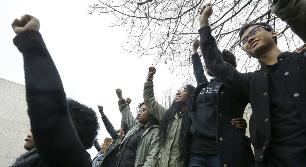 Students at Boston College raise their arms during a solidarity demonstration on the school's campus, Thursday, Nov. 12, 2015, in Newton, Mass. The protest was among numerous campus actions around the country following the racially charged strife at the University of Missouri. (Steven Senne/ AP)