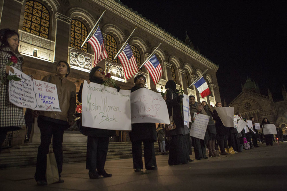 """A group of about two dozen Muslim women gathered outside the Boston Public Library in Copley Square to mourn the victims in Paris in what they called a """"silent vigil."""" (Jesse Costa/WBUR)"""