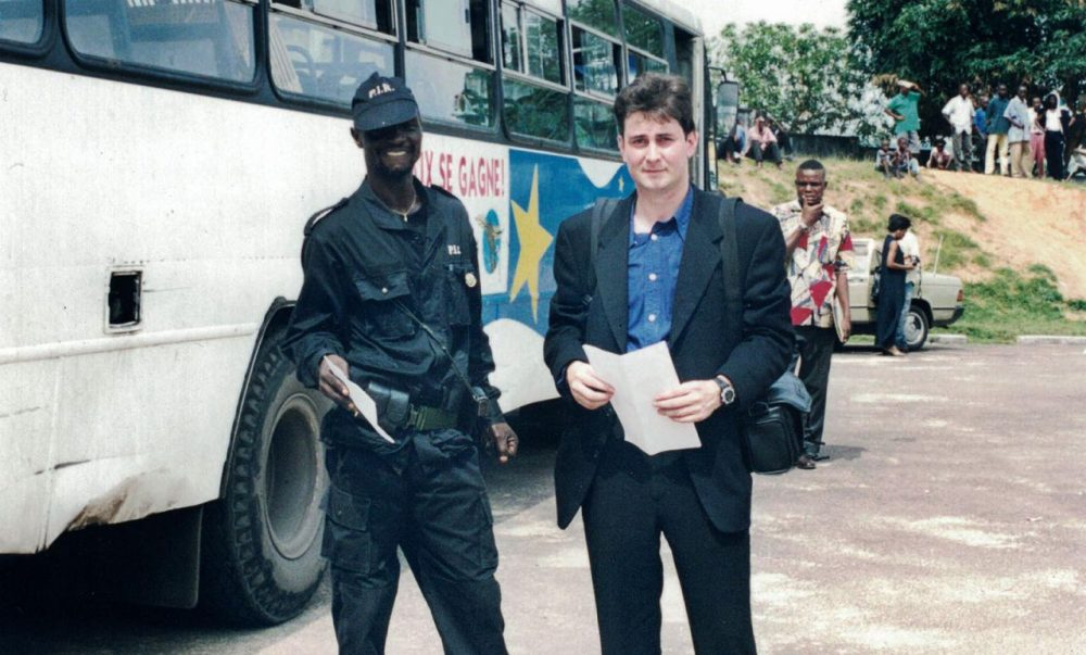 Sasha Chanoff stands next to a hired armed guard in the safe compound outside Kinshasa. (Courtesy)