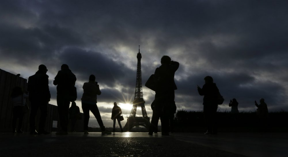 Julie Wittes Schlack: As the people of Paris and other terrorized cities resume normal life, we should consider whether our routines and distractions help us cope or help us adapt to the unacceptable. In this Sunday, Nov. 15, 2015 photo, tourists visit the Eiffel Tower in Paris, France. (Amr Nabil/ AP)
