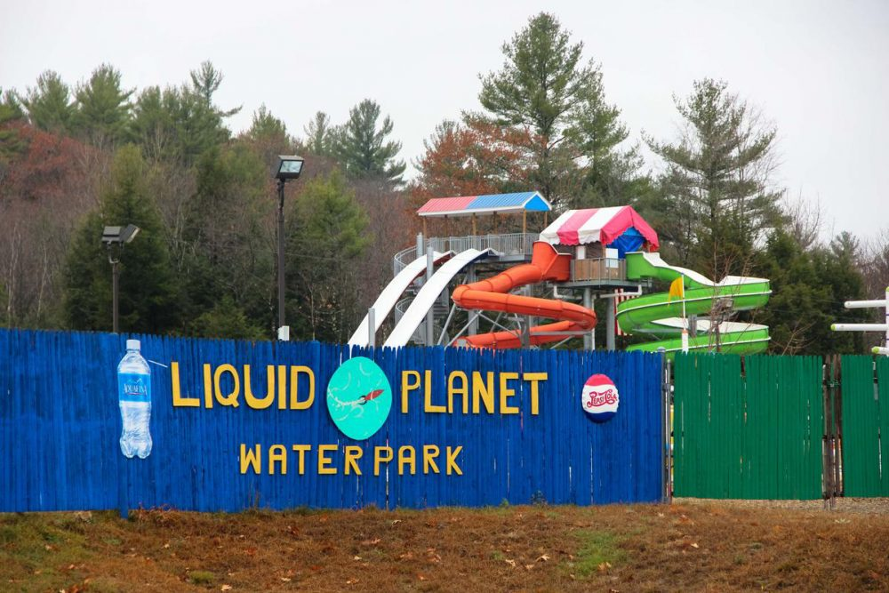 Two slides, one red, one green, coil downward from a 30 foot tall tower at Liquid Plant Water Park. (Sean Hurley/NHPR)