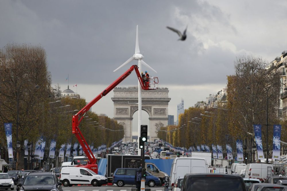 "Workers install a wind turbine on the Champs-Elysees avenue on November 26, 2015 in Paris, ahead of the 21st Session of the Conference of the Parties to the United Nations Framework Convention on Climate Change (COP21/CMP11), also known as ""Paris 2015"" from November 30 to December 11.  (Patrick Kovarik/AFP/Getty Images)"