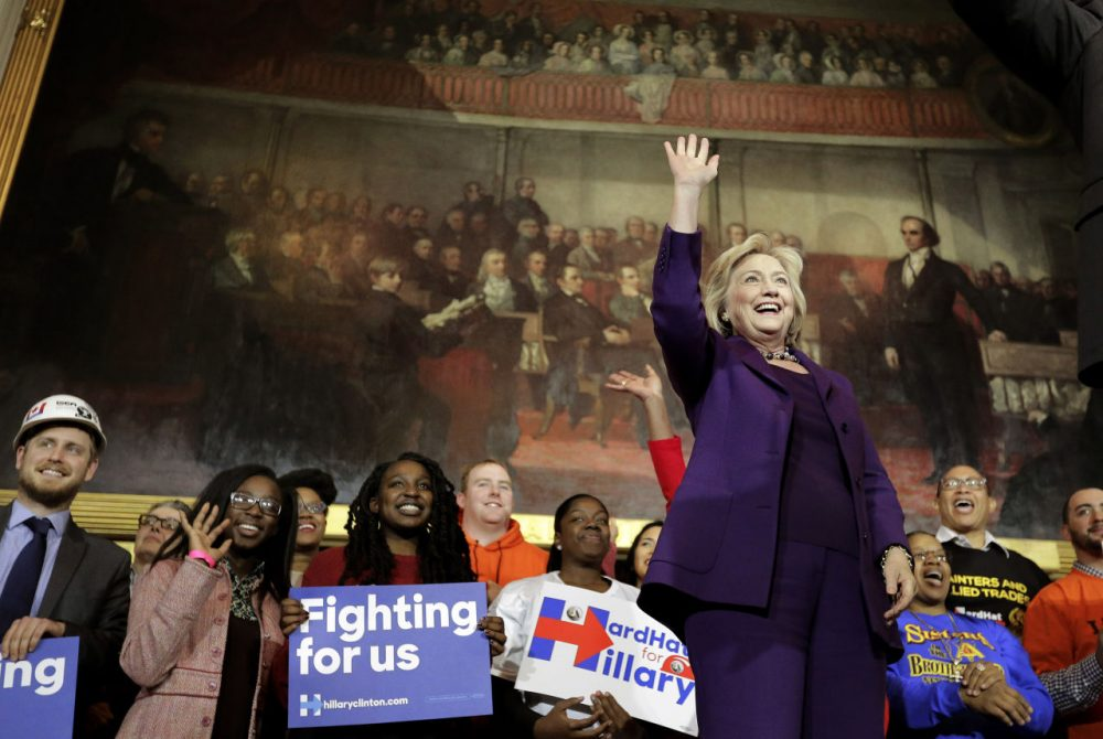 Democratic presidential candidate Hillary Clinton, right, stands on stage as she greets people at the start of a rally at Faneuil Hall. (Steven Senne/AP)