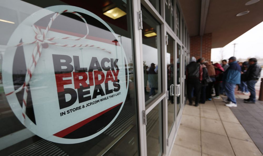 A sign promoting Black Friday specials is displayed in the window of a J.C. Penny store as shoppers queue up at the door for a 3 p.m. opening, Thursday, Nov. 26, 2015, in northeast Denver. The store opened two hours before other retailers to cash in on a flurry of bargain hunters, some who said that they waited for three hours to be one of the first people queued up outside. (David Zalubowski/AP Photo)