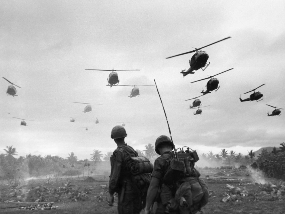 The second wave of combat helicopters of the 1st Air Cavalry Division fly over an RTO and his commander on an isolated landing zone during Operation Pershing, a search and destroy mission on the Bong Son Plain and An Lao Valley of South Vietnam, during the Vietnam War. The two American soldiers are waiting for the second wave to come in.  (Patrick Christain/Getty Images)
