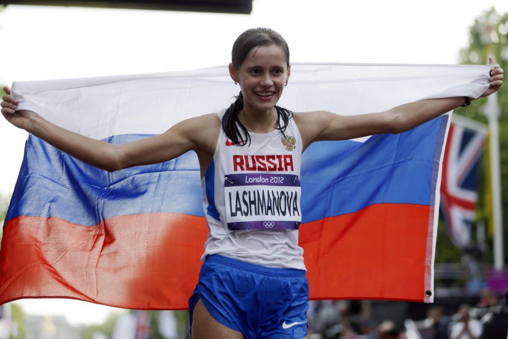 In this Saturday, Aug. 11, 2012 file photo, Russia's Elena Lashmanova celebrates after winning the gold medal in the women's 20-kilometer race walk at the 2012 Summer Olympics, in London. Two Russian Olympic medal hopefuls, including reigning women's race-walking champion Elena Lashmanova, could miss next year's Olympics as the IAAF investigates whether they competed while banned for doping. The new probe comes at a time when the IAAF and World Anti-Doping Agency are already investigating allegations of systematic doping and cover-ups in Russia. (AP Photo/Mike Groll, File)
