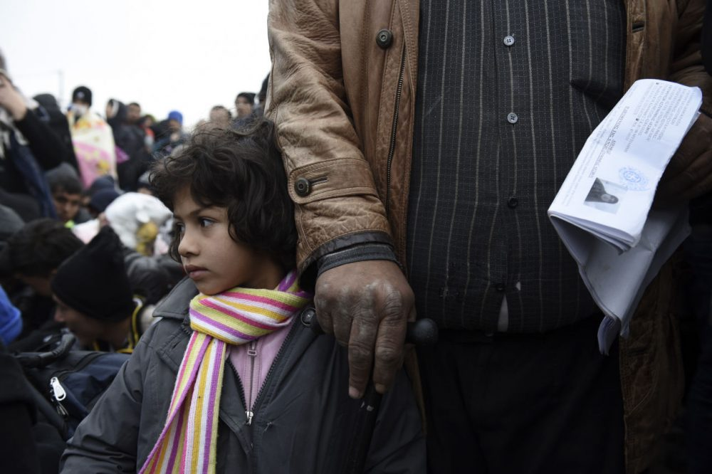 A Syrian girl with her father wait to be allowed by the Greek police to cross the borderline to Macedonia, near the village of Idomeni, Saturday, Nov. 21, 2015. Tempers have flared at Greece's main border crossing with Macedonia, where riot police pushed back thousands of migrants jostling to cross over, after Macedonia blocked access to people deemed to be economic migrants and not refugees. (AP Photo/Giannis Papanikos)