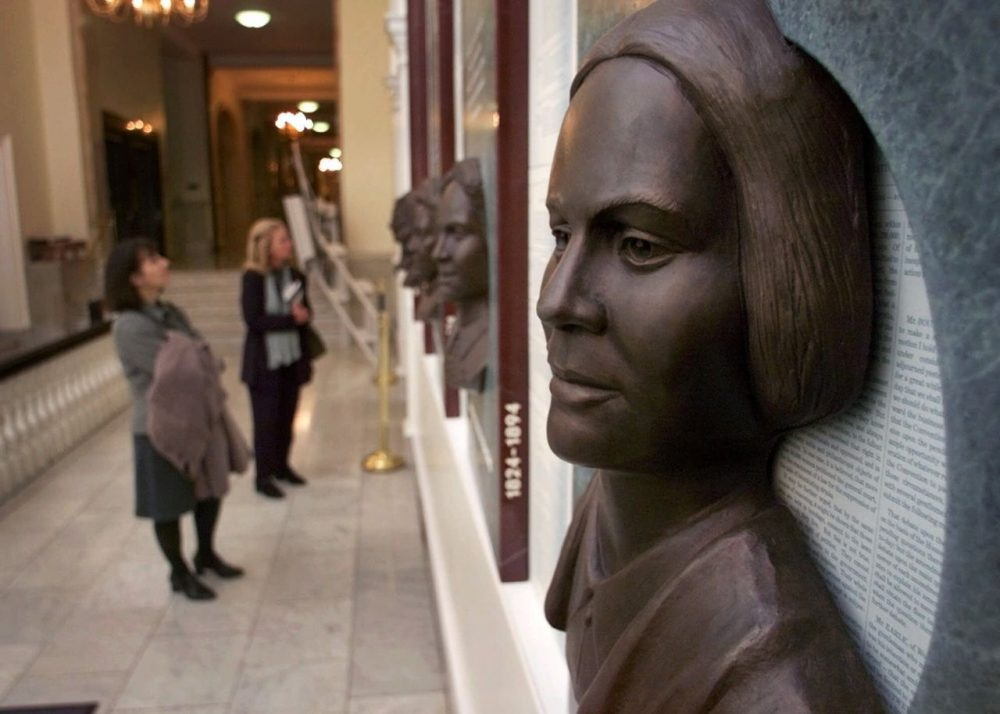 """Guests view a work of art titled """"Hear Us"""", featuring six bronze reliefs highlighting the contributions of women in public life in Massachusetts, at the Statehouse in Boston.  In the foreground is the likeness of Lucy Stone (Charles Krupa/AP)."""