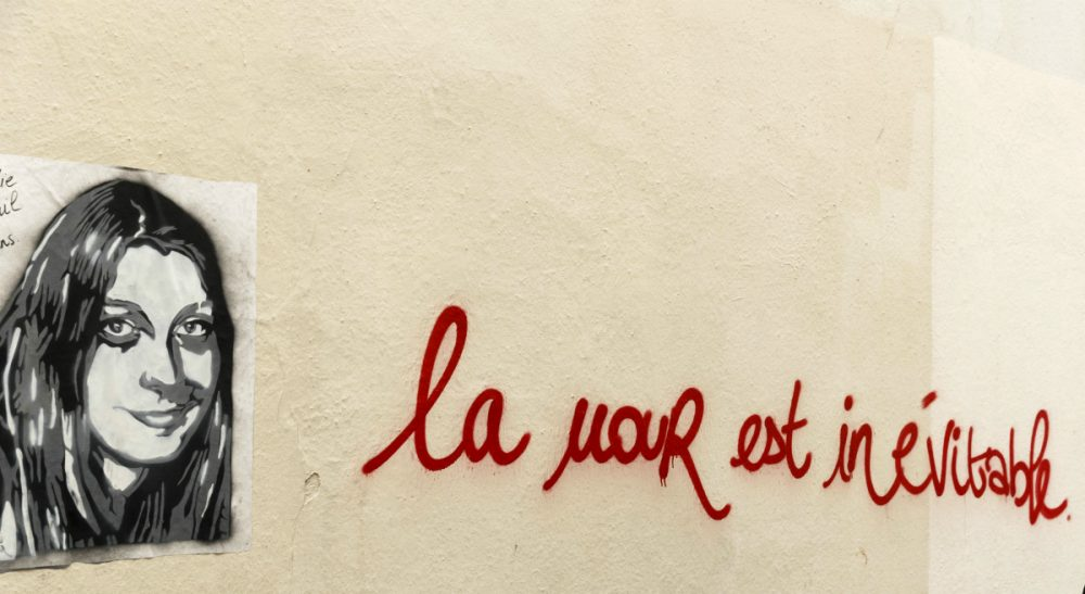 """Fabien Jobard: """"Those murdered last Friday were targeted for who they were, for how and where they lived."""" Pictured: Graffiti showing Paris attacks victim Elodie Breuil, in Paris, Tuesday, Nov. 17, 2015 . Breuil died in the shooting at the Bataclan concert hall last Friday. The writing is a play on words that reads: Love is inevitable. (Daniel Ochoa de Olza/AP)"""