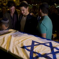 Friends of Ezra Schwartz, who was killed in a shooting attack in the West Bank that claimed two other lives, stand next to his coffin during a private ceremony at Ben Gurion Airport near Tel Aviv, Israel, Saturday, Nov. 21, 2015. Schwartz's body was repatriated to Boston for burial. (Oded Balilty/AP)