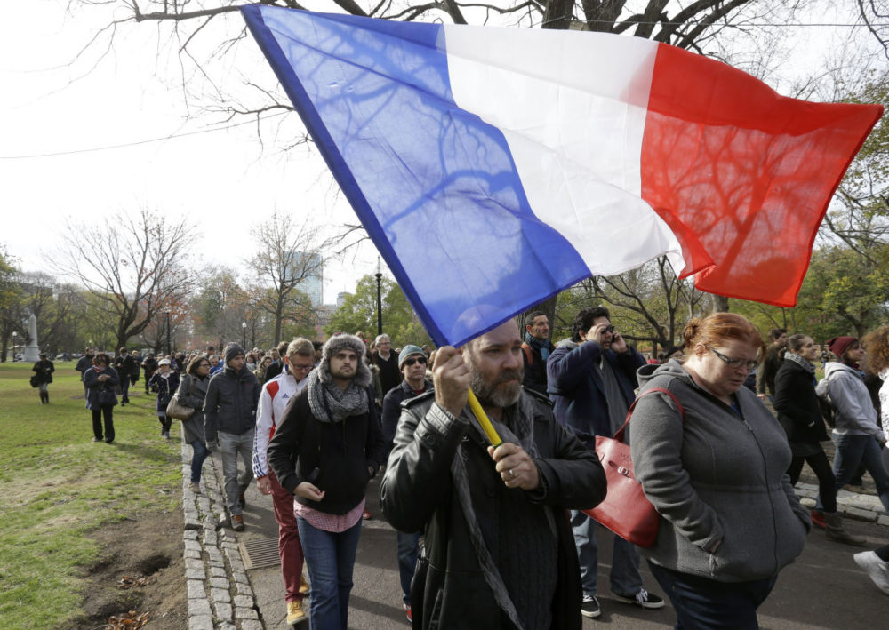 Austin Wolfe, of Quincy, Mass., who holds both U.S. and French citizenship, carries a French flag at a vigil Sunday in Boston, held in sympathy for the people of Paris. (Steven Senne/AP)