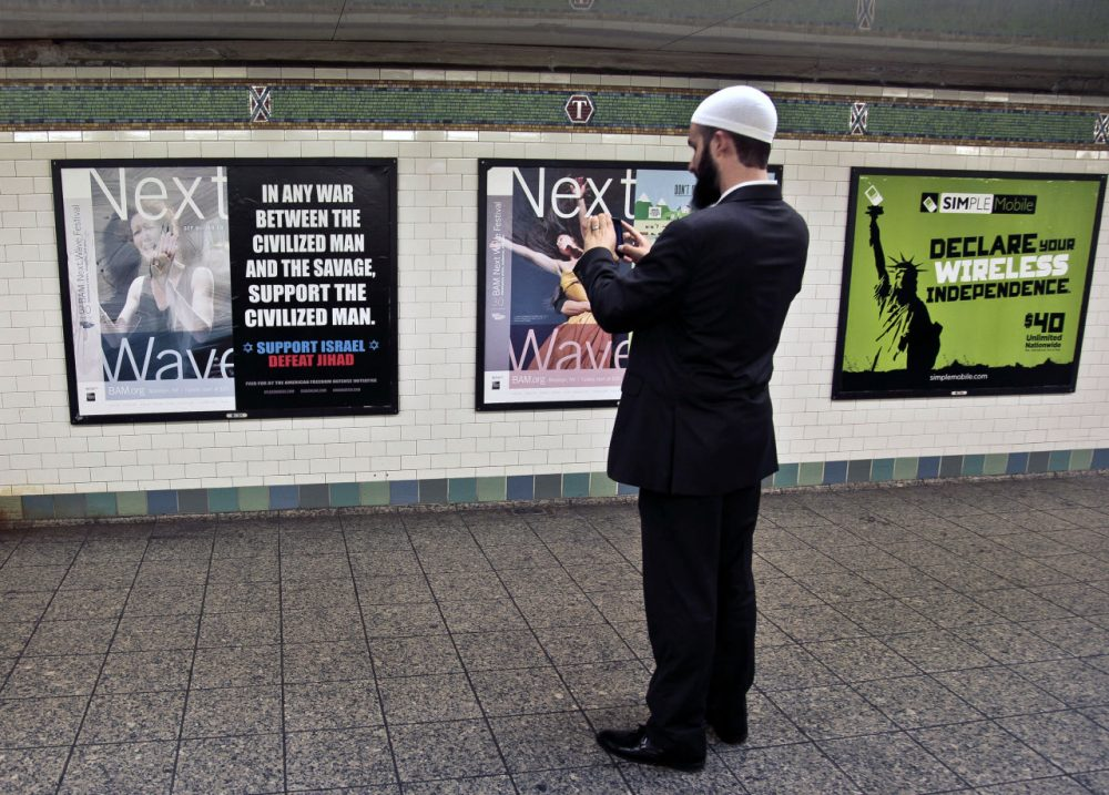 The MBTA banned ads on the T about political, social, or religious issues on Monday. Pictured here is Cyrus McGoldrick, Advocacy Director for Council on American-Islamic Relations, taking a photo of an anti-Muslim that, in 2012, sparked a similar controversy in New York, leading the MTA to ban all political and religious ads. (AP Photo/Bebeto Matthews)