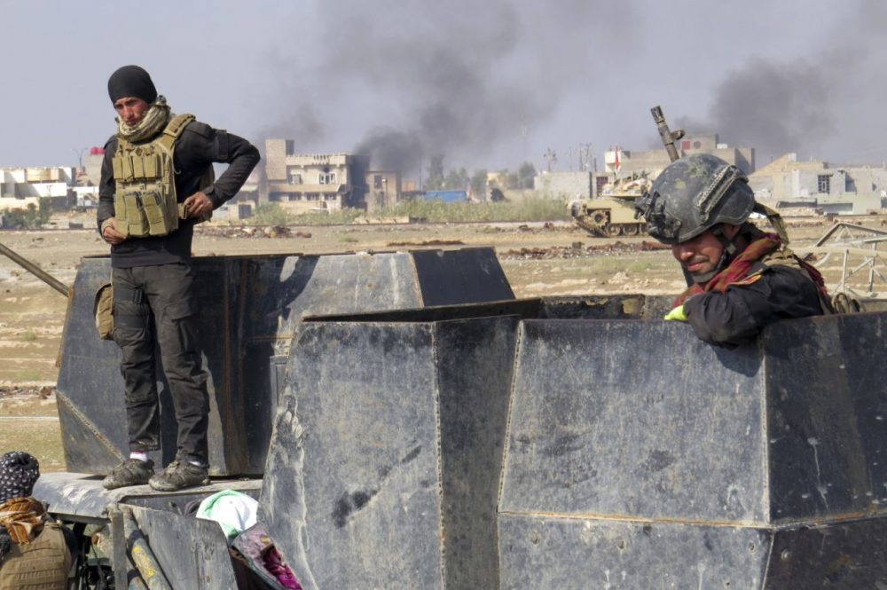 Iraqi forces supported by U.S.-led coalition airstrikes advance their position during clashes with Islamic State group in the western suburbs of Ramadi, the capital of Iraq's Anbar province, 70 miles west of Baghdad, Iraq, Saturday, Nov. 21, 2015. (Osama Sami/AP)