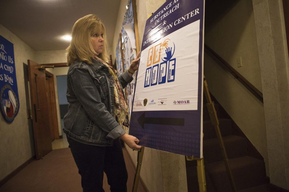 Susan Silva sets up an East Bridgewater H.O.P.E. sign at the Community Covenant Church where the non-profit hosts Substance Abuse Outreach and Intervention Center nights. (Jesse Costa/WBUR)