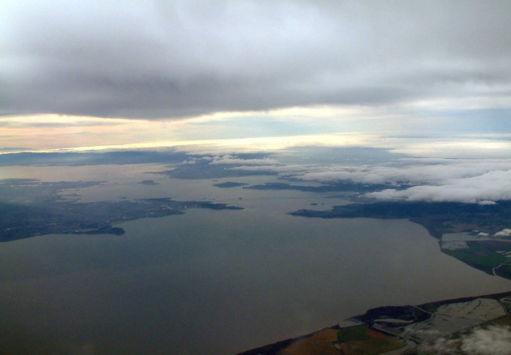 A view out the window of the NOAA research plane, with the Richmond-San Rafael Bridge in the distance. The plane is gaining altitude to fly into the storm cloud. (Danielle Venton/KQED)