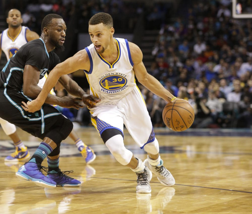 Golden State Warriors guard Stephen Curry, left, drives past Charlotte Hornets guard Kemba Walker in the second half of an NBA basketball game Wednesday, Dec. 2, 2015 in Charlotte, N.C. Golden State won 116-99. (Nell Redmond/AP)