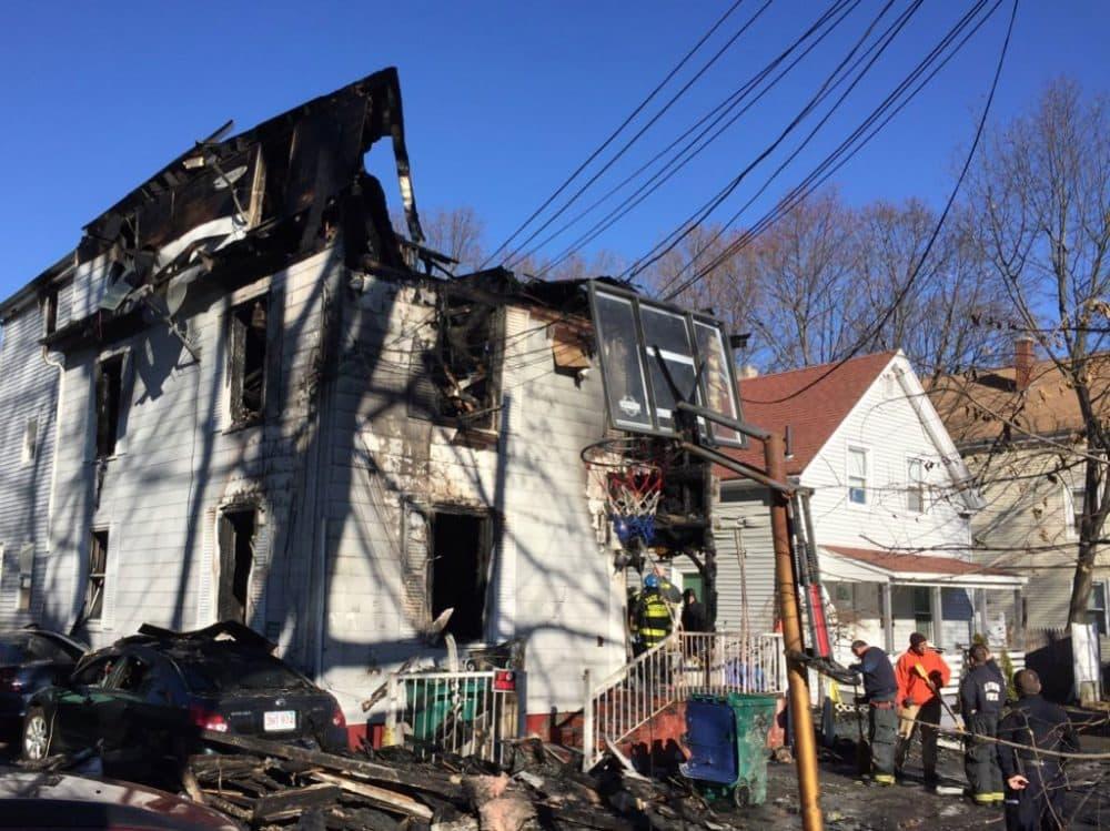 Officials examine a Lynn building where a fire killed four people. (Curt Nickisch/WBUR)