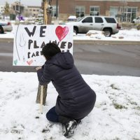 Bethany Winder, a nurse who lives in Colorado Springs, Colo., plants a sign in support of Planned Parenthood just south of its clinic as police investigators gather evidence near the scene of Friday's shooting at the clinic Sunday, Nov. 29, 2015, in northwest Colorado Springs. (David Zalubowski/ AP)