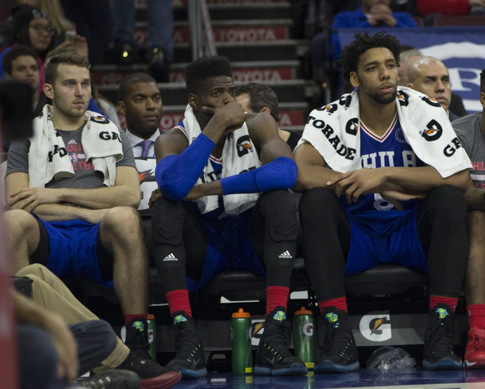 PHILADELPHIA, PA - OCTOBER 30: Nik Stauskas #11, Nerlens Noel #4, and Jahlil Okafor #8 of the Philadelphia 76ers watch the final minutes of the game against the Utah Jazz from the bench on October 30, 2015 at the Wells Fargo Center in Philadelphia, Pennsylvania. (Mitchell Leff/Getty Images)