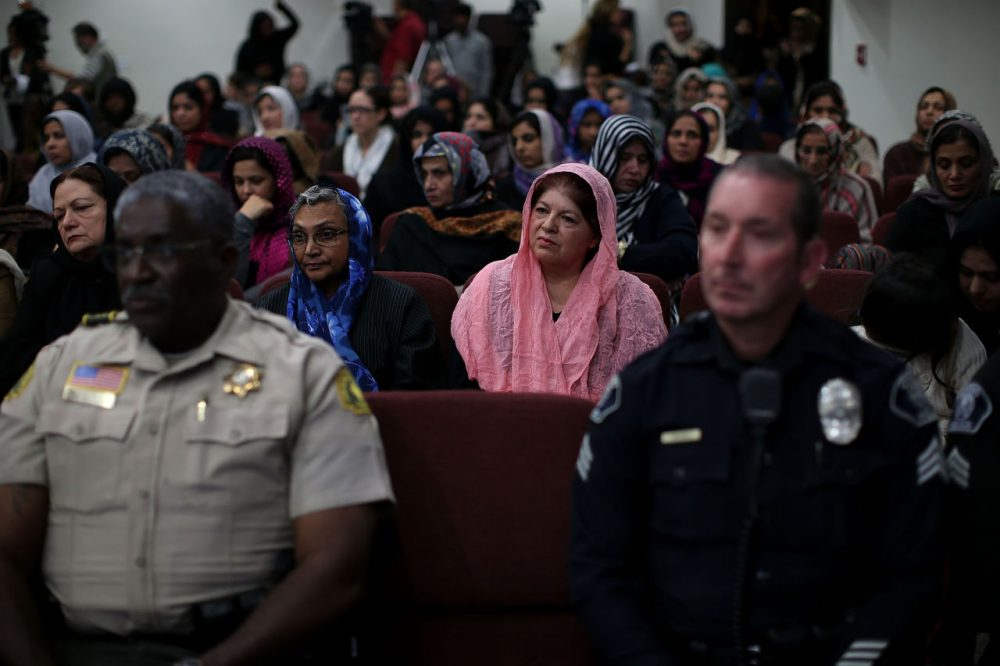 Muslim women sit behind police officers during a prayer vigil at Baitul Hameed Mosque on December 3, 2015 in Chino, California, a day after the mass shooting at the Inland Regional Center in San Bernardino that left at least 14 people dead.  (Justin Sullivan/Getty Images)