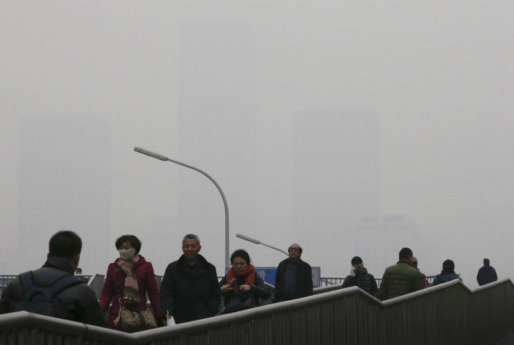 People walk on a pedestrian overhead bridge as office buildings in Central Business District of Beijing are shrouded with heavy haze, Tuesday, Dec. 8, 2015. Beijing's red alerts for smog are as much about duration as they are about severity of pollution forecasts. The forecasting model must predict three or more days of smog with levels of 300 or higher on the city's air quality index - which typically would include having levels of dangerous PM 2.5 particles of about 10 times the safe level. (Andy Wong/AP Photo)