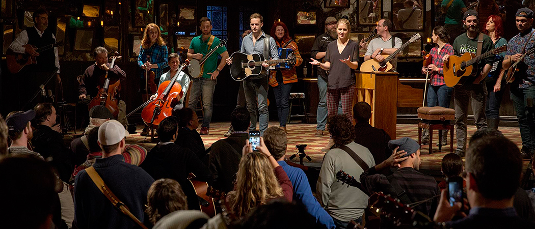 """Actors Stuart Ward, center, and Dani de Waal talk with a group of guitarists before playing """"Falling Slowly"""" on the stage of """"Once"""" at the Shubert Theatre on Wednesday. (Robin Lubbock/WBUR)"""