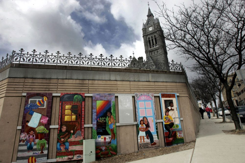 """A mural titled, """"Neighbors of Holyoke"""" in front of City Hall's spire, background in Holyoke. (Chitose Suzuki/AP)"""