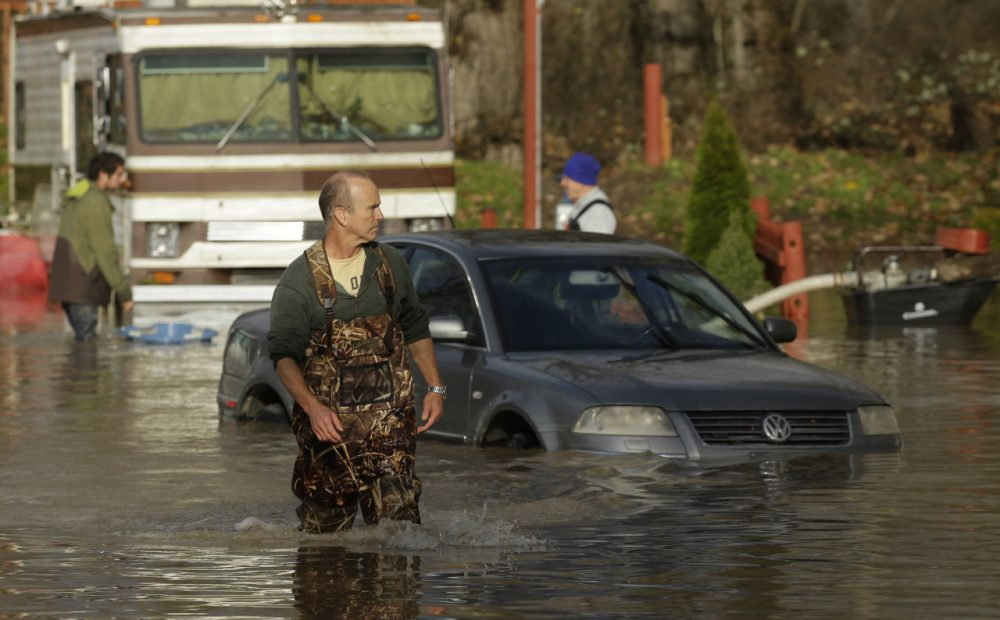 Kevin McLeod, co-owner of the Riverview RV Park, wades through floodwaters near a partially submerged car Wednesday, Dec. 9, 2015, after he hooked up a pump to get rid of water that flooded RV's and other vehicles Wednesday morning in Puyallup, Wash. The National Weather Service says wind and rain are expected to slow Wednesday, but snow may continue to fall in the mountains. (Ted S. Warren/AP)