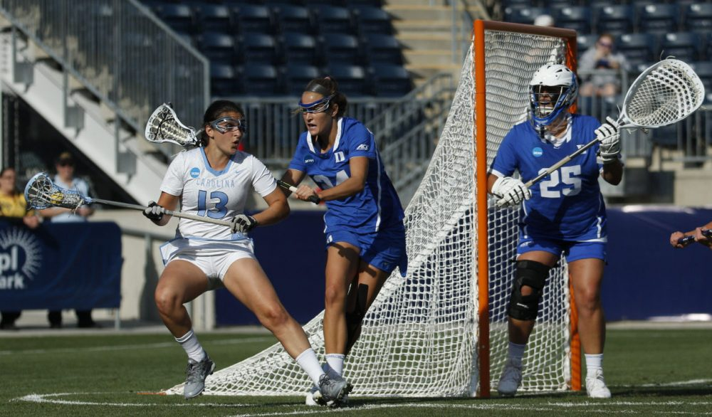 North Carolina's attack/midfield Sammy Jo Tracy, left, tries to get past Duke's midfielder Katie Trees, center, as goalie Kelsey Duryea, right, looks on during the first half of the semifinals in the NCAA Division I women's lacrosse tournament, Friday, May 22, 2015, in Chester. (AP Photo/Chris Szagola)