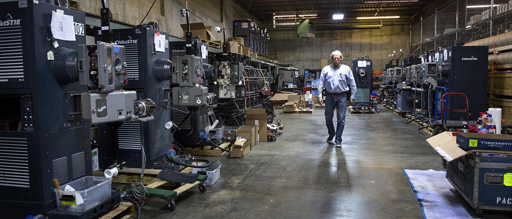 Chapin Cutler walks past a row of 70 mm film projectors at Boston Light and Sound's offices in Brighton. (Robin Lubbock/WBUR)