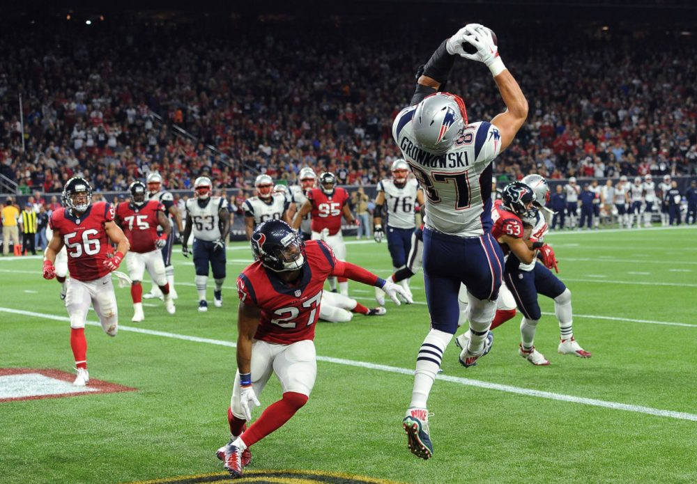New England Patriots tight end Rob Gronkowski (87) catches a pass for a touchdown over Houston Texans strong safety Quintin Demps (27) during the game last night. Patriots won 27-6 to clinch a spot in the playoffs. (George Bridges/AP)