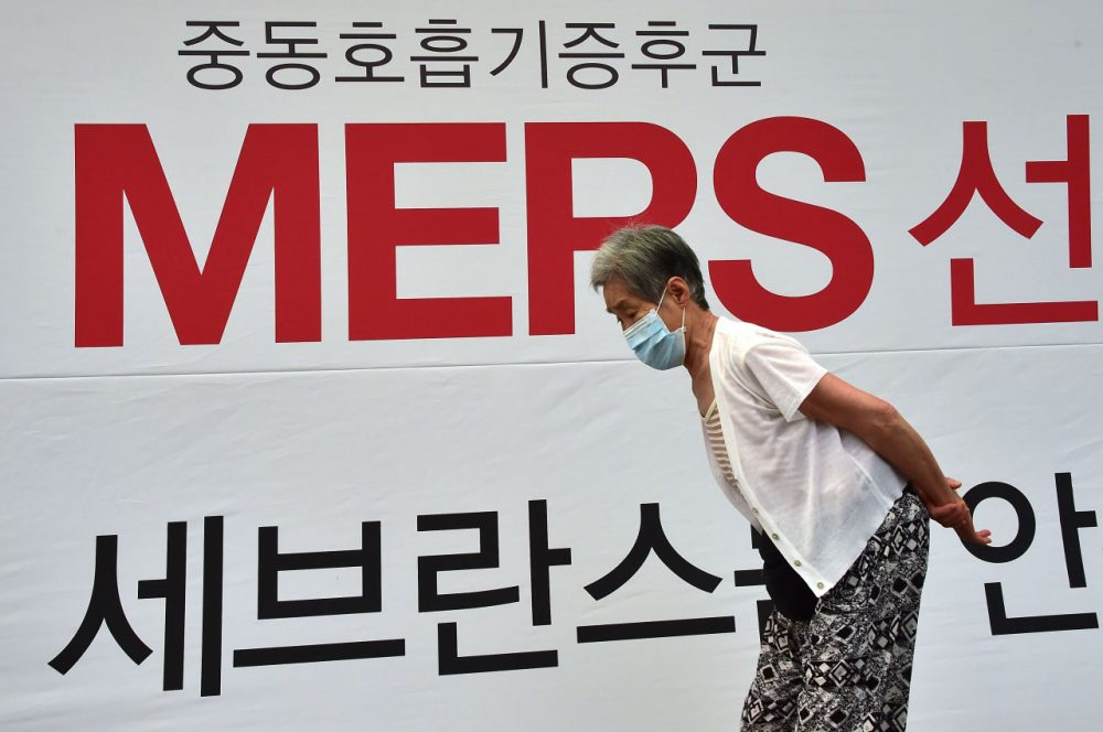 An elderly woman wearing a face mask walks past signage on MERS at Severance Hospital in Seoul on June 16, 2015. South Korea on June 16 reported three more fatalities from the MERS outbreak but health authorities said they were cautiously optimistic the worst was over as the number of new cases was falling. (Jung Yeon-Je/AFP/Getty Images)