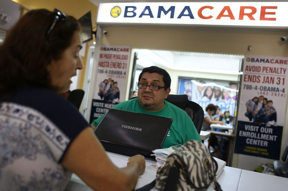 Martha Lucia (left) sits with Rudy Figueroa, an insurance agent from Sunshine Life and Health Advisors, as she picks an insurance plan available in the third year of the Affordable Care Act at a setup in the Mall of the Americas in Miami. (Joe Raedle/Getty Images)