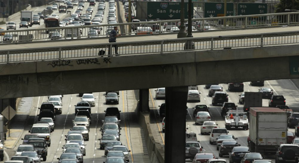 Earlier this month, in a rare showing of bipartisan compromise, Congress passed a $305 billion measure to fund roads, bridges and rail lines. In this May 6, 2015 photo, a man walks on the Wilshire Boulevard overpass as traffic slowly moves along the 110 Freeway in downtown Los Angeles. (Jae C. Hong/ AP)