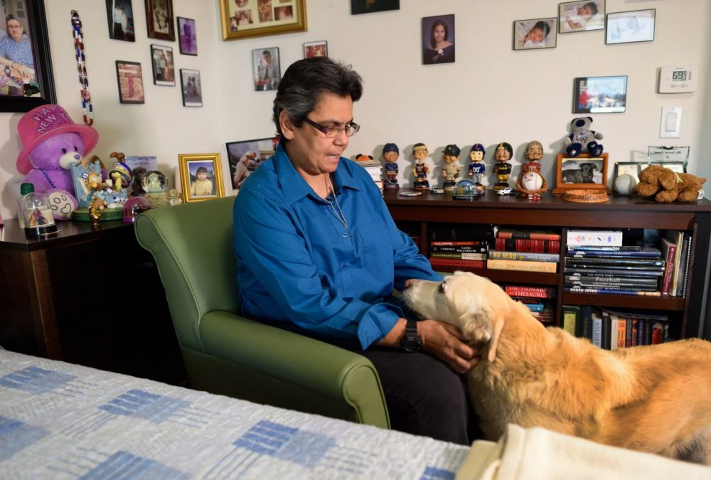 Disabled veteran Gloria Montes pets her dog Cache in her Bronx apartment November 9, 2015 in New York. Montes, who was forced to sleep in a car or on friends' floors until she found a place at a housing unit in the Bronx in September 2014, says she wants the military to do more to help veterans adjust to civilian life, and navigate the benefits that are open to them. (Don Emmert/AFP/Getty Images)