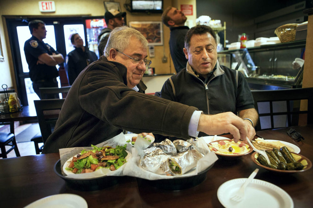 Camille Nasrah, left, and Salah Asfoura -- both Syrian nationals living in Worcester -- eat lunch at Bahnan's International Marketplace. (Jesse Costa/WBUR)