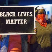 Demonstrators, marking the one-year anniversary of the shooting of Michael Brown, protest along West Florrisant Street on August 10, 2015 in Ferguson, Missouri. Brown was shot and killed by a Ferguson police officer on August 9, 2014. His death sparked months of sometimes violent protests in Ferguson and drew nationwide focus on police treatment of black suspects.  (Scott Olson/Getty Images)