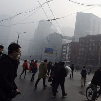 People cross a road on a polluted day in Beijing on December 14. Authorities issued the second red alert for smog this month today. (Greg Baker/AFP/Getty Images)