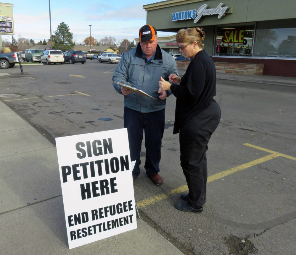 Rick Martin has been collecting signatures for his initiative to ban refugee centers in Twin Falls County, Idaho. Here, Marie Christopherson of Buhl, Idaho stopped to sign. (Tom Banse/Northwest News Network)