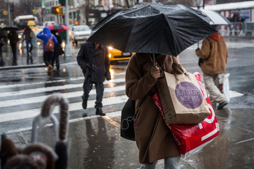 People walk along the sidewalk in the rain on Christmas Eve on December 24, 2014 in New York City. (Andrew Burton/Getty Images)