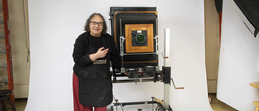 A fixture in Cambridge for decades and known for portraits often described as capturing the soul of her subjects, Esla Dorfman is taking her last shots. Here, Dorfman stands with her huge  20x24 Polaroid camera in her Cambridge studio. (Jesse Costa/WBUR)