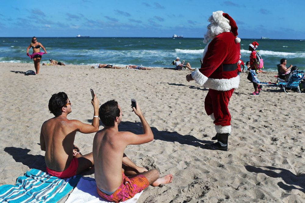 Timmy McGovern (dressed as Santa Claus) walks along the beach passing out candy canes and posing for pictures with beach goers on December 21 in Fort Lauderdale, Florida. Santa Claus has been visiting the beach just before Christmas for over 30 years.  (Joe Raedle/Getty Images)